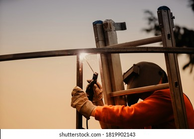 A structural steel worker working on a high rooftop for a modern house roof structure installation - Shutterstock ID 1819902143