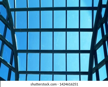 The structure of the roof with clear glass. Glass roof and blue sky with steel structure.