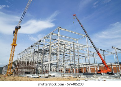 Structure of steel roof frame installation by mobile crane under the building in construction with blue sky