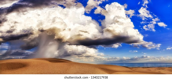 Structured and layered clouds over sand dunes of Stockton beach in Australia with strong storm raining down on earth from blue skies.