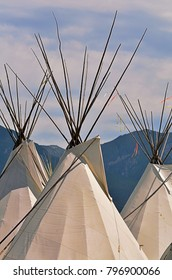 Structures of traditional lodging of North American First Peoples (Native Americans/American Indians) from Plains regions. Tops of lodges at powwow encampment.