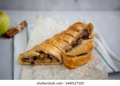 strudel with apple and cinnamon on a light towel, light background