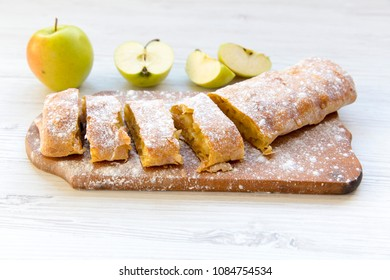 Strudel or apple pie on wooden board. Side view. Closeup.
