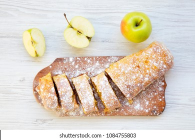 Strudel or apple pie on wooden board. Top view. Closeup.