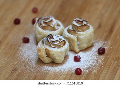 Strudel with apples and cranberries. bun with apples and cranberries sprinkled with powdered sugar on wood background. Variation apple strudel summer pie. Summer breakfast.