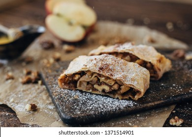 Strudel with apples and nuts. Composition  of delicious bakery products. Apple pie, cinnamon, honey, apples and walnuts.