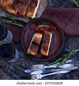 Strudel with cheese and sun-dried tomatoes.  The table is set for dinner. Lunch. Homemade pie, strudel and snacks, vegetables, fruits, cheese.