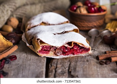 Strudel with a cherry. Cherry pie. Food on the nature.  Pie, strudel with berries  With autumn decor. Cozy food. Style rustic. Autumn still life.