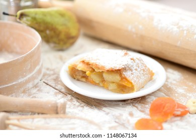 strudel (roll strudel) with apple and apricot on a wooden board with flour