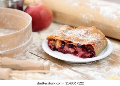 strudel (roll strudel) with apple and currant on a wooden board with flour