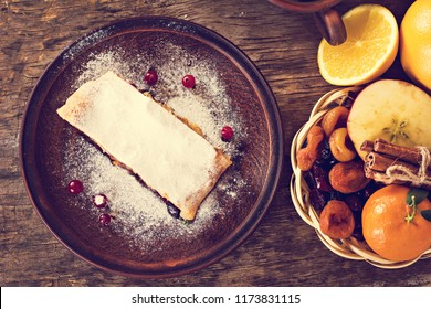strudel and winter decor. Apple strudel (pie) with dried fruits, oranges, cranberries, walnuts and powdered sugar. Rustic style.