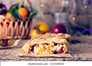 strudel and winter decor. Christmas homemade pastry. Apple strudel (pie) with dried fruits, oranges, cranberries, walnuts and powdered sugar with Christmas decor close up.  Rustic style.