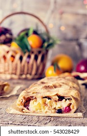 strudel and winter decor. Christmas homemade pastry. Apple strudel (pie) with dried fruits, oranges, cranberries, walnuts and powdered sugar with Christmas decor close up. Winter decor. Rustic style.