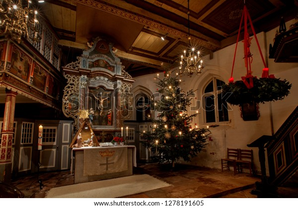 Strueckhausen, Germany - January 06, 2019: Altar of the historic church named St. Johannis with festive christmas tree, candles, advent wreath and decoration at night