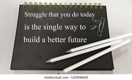 Struggle that you did today is the single way to build a better future memo written on a notebook with pencil and paper clip