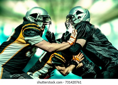 Struggling football player pushing each other in front of a light flooded background