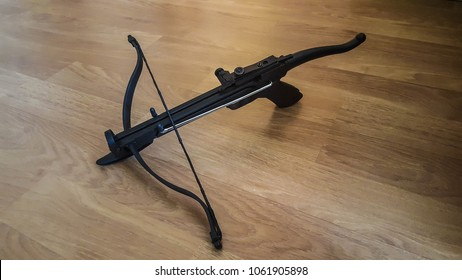 A strung hand crossbow on a wooden background. It has an arming lever