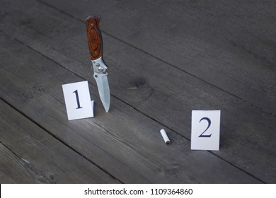 Stub and folding knife on a wooden background, evidence and investigation, close-up