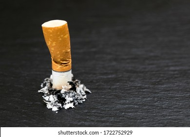 Stubbed cigarette butt stub with ash on black background