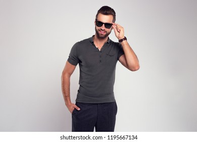 Stubble macho man. Handsome young man in sunglasses looking at camera while standing against white background