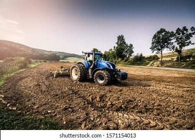 Stubble-tillage cultivation after harvest with big blue modern tractor aggregated with yellow equipment. Tractor using GPS for precision navigation onward the field.