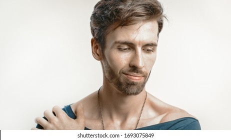 Stubbly Macho Looks Down Smiling Sensually Or Shyly While Touching His Shoulder With Hand, Head And Shoulders Studio Portrait Of Cheerful Caucasian Man, Male Beauty Concept