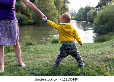 a stubborn boy, pulling his mother's hand as a bad attitude in terrible two period; green gras and river background on a sunny summer day
