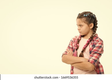 Stubborn child. Disagreement and stubbornness. Girl serious face offended. Kid looks strictly. Girl folded arms on chest looks serious copy space white background. Stubborn temper. Stubborn concept.