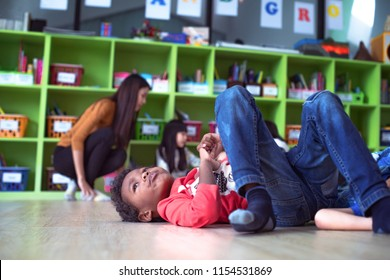 A stubborn intractable and naughty boy kids in classroom at kindergarten pre school anti learning gives headache to woman teacher. Uncontrolled if boys kids behaviour