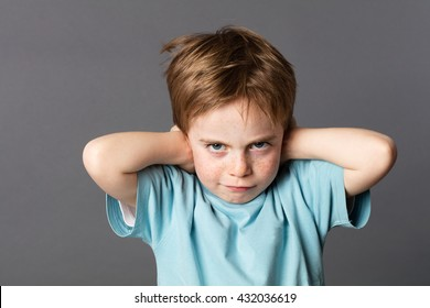 stubborn young kid with freckles teasing, covering his closed ears, ignoring his parent scolding with attitude, asking for silence, grey background