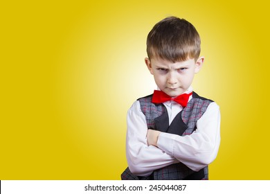 Stubborn,sad,upset  little boy,child  isolated over yellow background.Facial expression