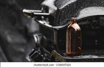 Stubby beer bottle and barbecue in the pouring rain