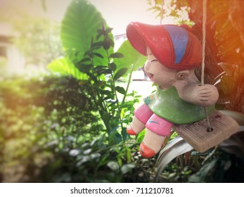 Stucco doll with swing shape for garden decoration. Smiling boy
