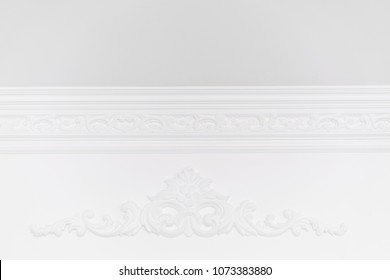 Stucco elements on white wall. Luxury design with mouldings. Beautiful ornate white decorative plaster in studio