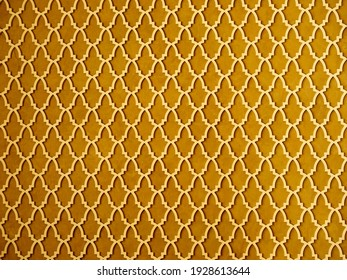 Stucco with geometric ornament in arabic style on wall surface. Golden background with arabesques or symmery orient decor with arch pattern in shades of Fortuna Gold color. - Shutterstock ID 1928613644