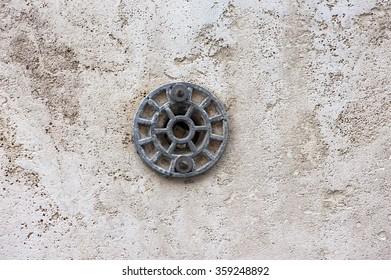 stucco wall with hidden paper in the hole under metal bar