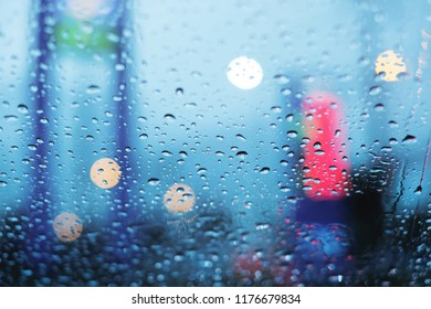 Stuck in traffic on rainy day, droplets on the windshield with blurry and Bokeh background.