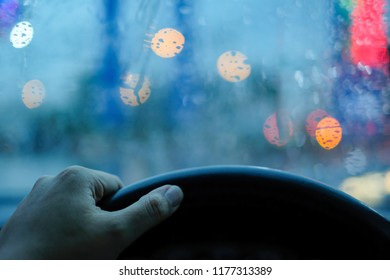 Stuck in traffic on rainy day, hand grabbing steering wheel and droplets on the windshield with blurry Bokeh in background.