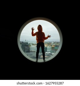 Stuck trapped and longing out of here. Child looking out over modern civilization.