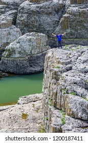 STUDEN KLADENETZ, BULGARIA - MAY 2, 2015: Adult male in blue t-shirt and black hat greets by spreading arms on cliffs at Devil Canyon natural phenomenon also known as Sheytan Dere in sunny spring day