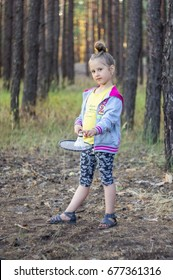 STUDENOK, UKRAINE - JULY 08, 2017: Little girl in a pine forest playing badminton
