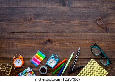 Student accessories. School or student's stationery mockup with glasses, alarm clock, notebook on dark wooden background top view copy space