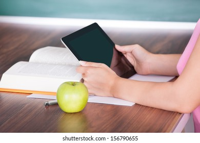 Student with apple and book on desk holding digital tablet