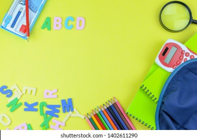 Student backpack and various school supplies. Studying, education and back to school concept. Yellow background and selective focus.