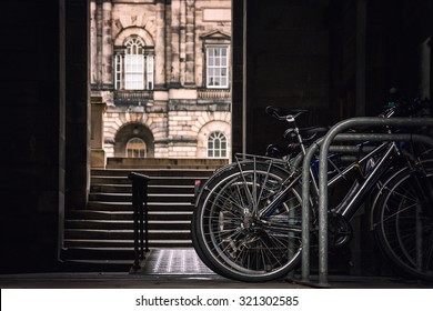 Student bikes on a rack with a view of Edinburgh University in the background. Retro style processing and intentional selective focus on the bikes.