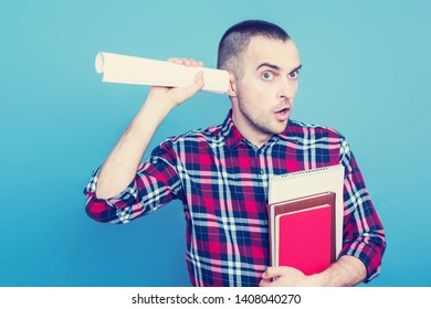 Student with books, guy eavesdropping, portrait, blue background, copy space, slogan, toned