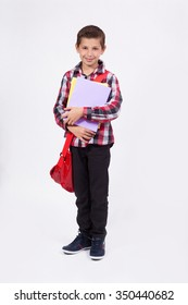 student with books in hand and a backpack on a white background laughing and looking at the camera.