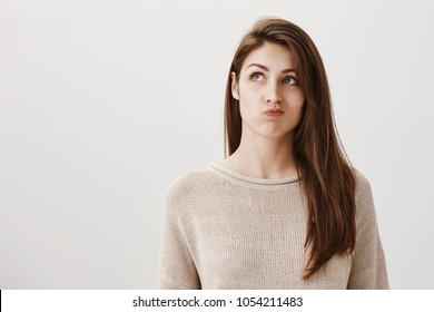 Student is bored making up ideas what to do. Portrait of carefree dreamy caucasian girl looking up with puckered lips, thinking how to entertain herself, wanting to call friend over gray background