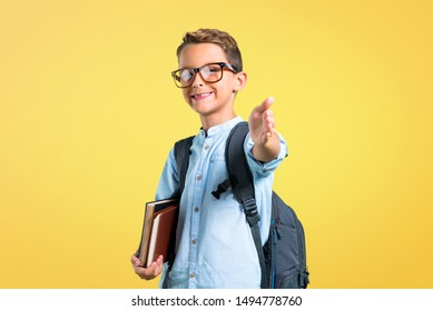 Student boy with backpack and glasses handshaking after good deal on yellow background