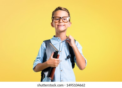 Student boy with backpack and glasses proud and self-satisfied in love yourself concept on yellow background